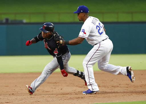 Cleveland Indians' Jose Ramirez, left, is tagged out by Texas Rangers third baseman Adrian Beltre (29) as Ramirez attempted to reach third after a single and a fielding error during the fifth inning of a baseball game, Saturday, July 21, 2018, in Arlington, Texas.