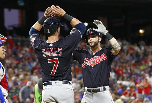 Cleveland Indians' Tyler Naquin, right, celebrates his two-run home run with Yan Gomes (7)  during the sixth inning of a baseball game against the Texas Rangers, Saturday, July 21, 2018, in Arlington, Texas.