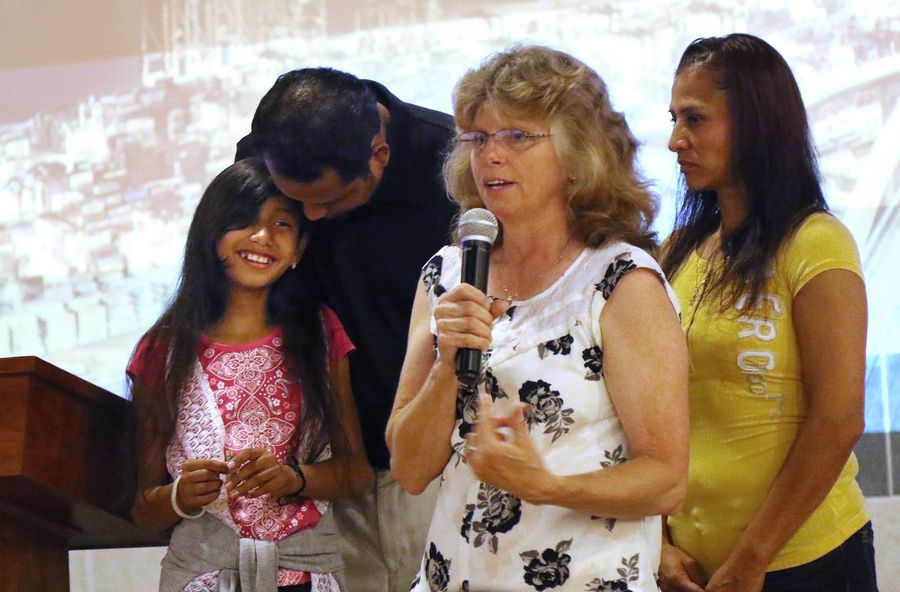 Sue Elleson talks about the outpouring of community support as displaced Prospect Heights resident Winer Aguirre hugs his daughter, Jeimy, 10, next to his wife, Sonia, during a special healing service Sunday at Lakewood Chapel in Arlington Heights.