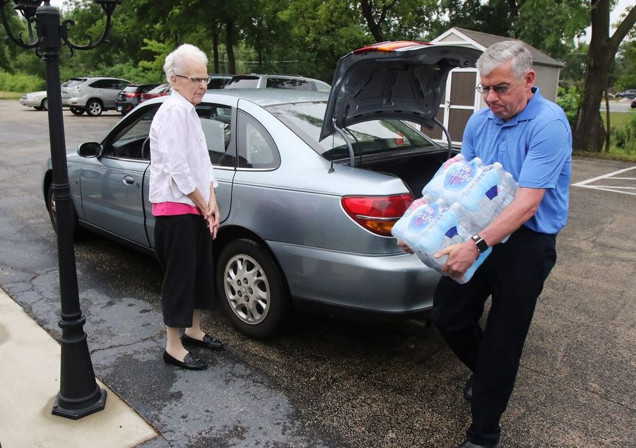 Church member Doug Nichols unloads bottles of water donated by Kay Sullivan of Arlington Heights during a special healing service Sunday at Lakewood Chapel in Arlington Heights.