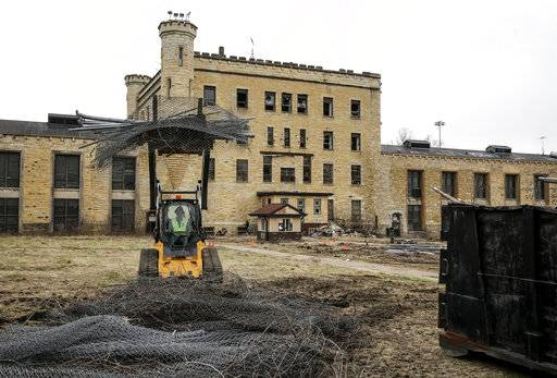 In this April 21, 2018 photo, the remains of an old fence pile up on the prison yard during the first cleanup day at the former Collins Street prison in Joliet, Ill. The correctional facility, which opened in 1858, was shuttered in 2002. Nearly two decades later, the city of Joliet plans to improve the facility by opening it to the public. The Joliet Area Historical Museum is budgeting for a profit from tours and other income expected from the opening of the old Joliet prison. The prison grand opening on Aug. 25, 2018, is getting unexpected international attention. Eric Ginnard (Eric Ginnard/Herald-News via AP)