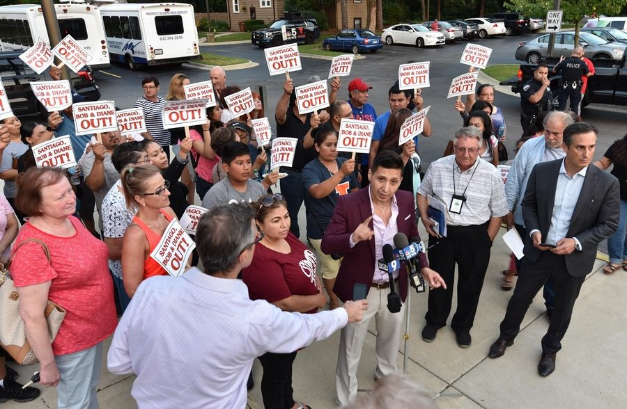 Condo co-owner Francisco Ruiz, of Streamwood, speaks to the media after a meeting Monday held by the River Trails condominium association board in the wake of last week's massive fire in Prospect Heights. Behind him, some condo residents hold signs calling for the resignation of three board members.