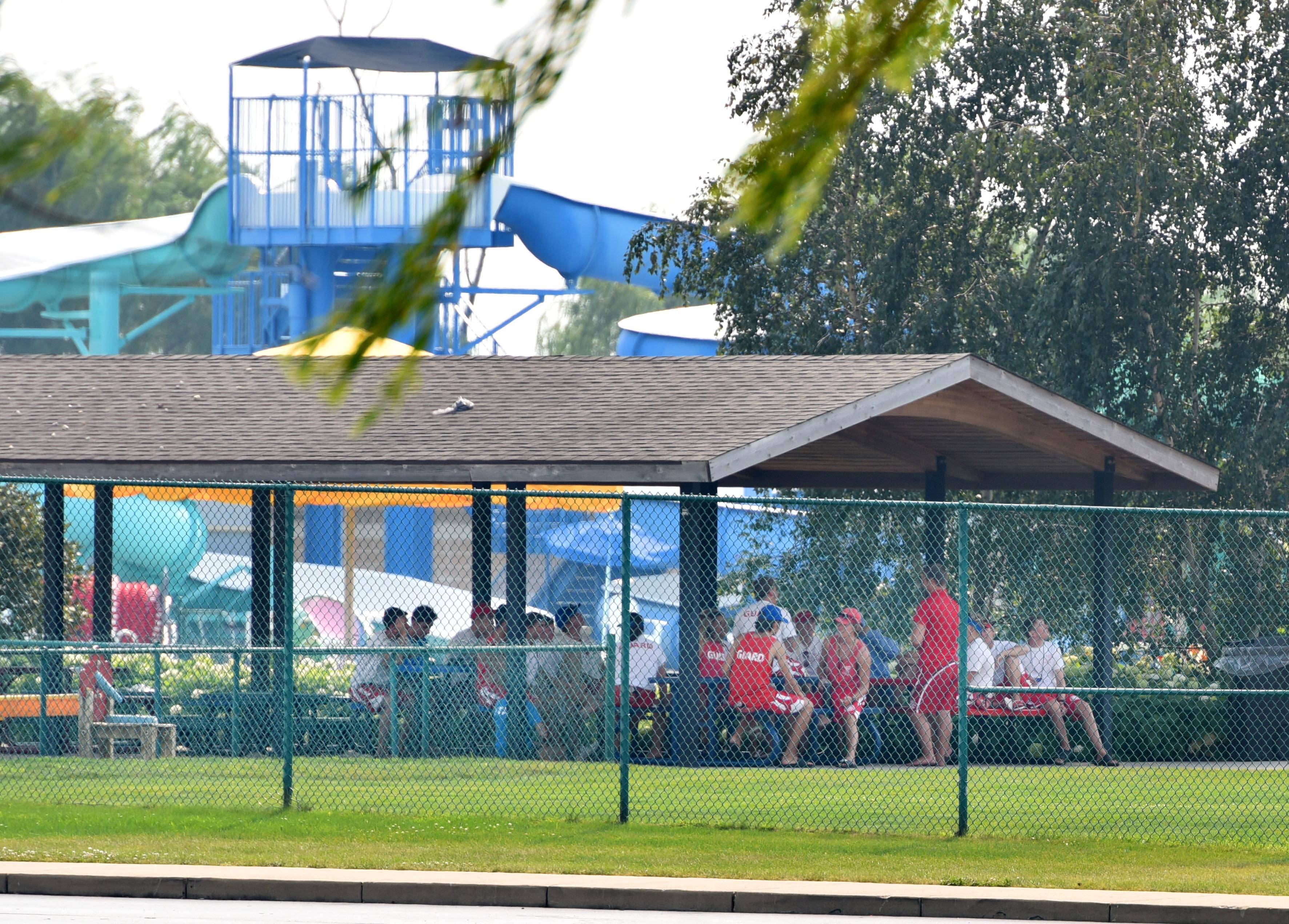 Staff members gather at picnic tables Monday afternoon at Stingray Bay Aquatic Center in Huntley where two swimmers were pulled from the water by lifeguards for being in distress.