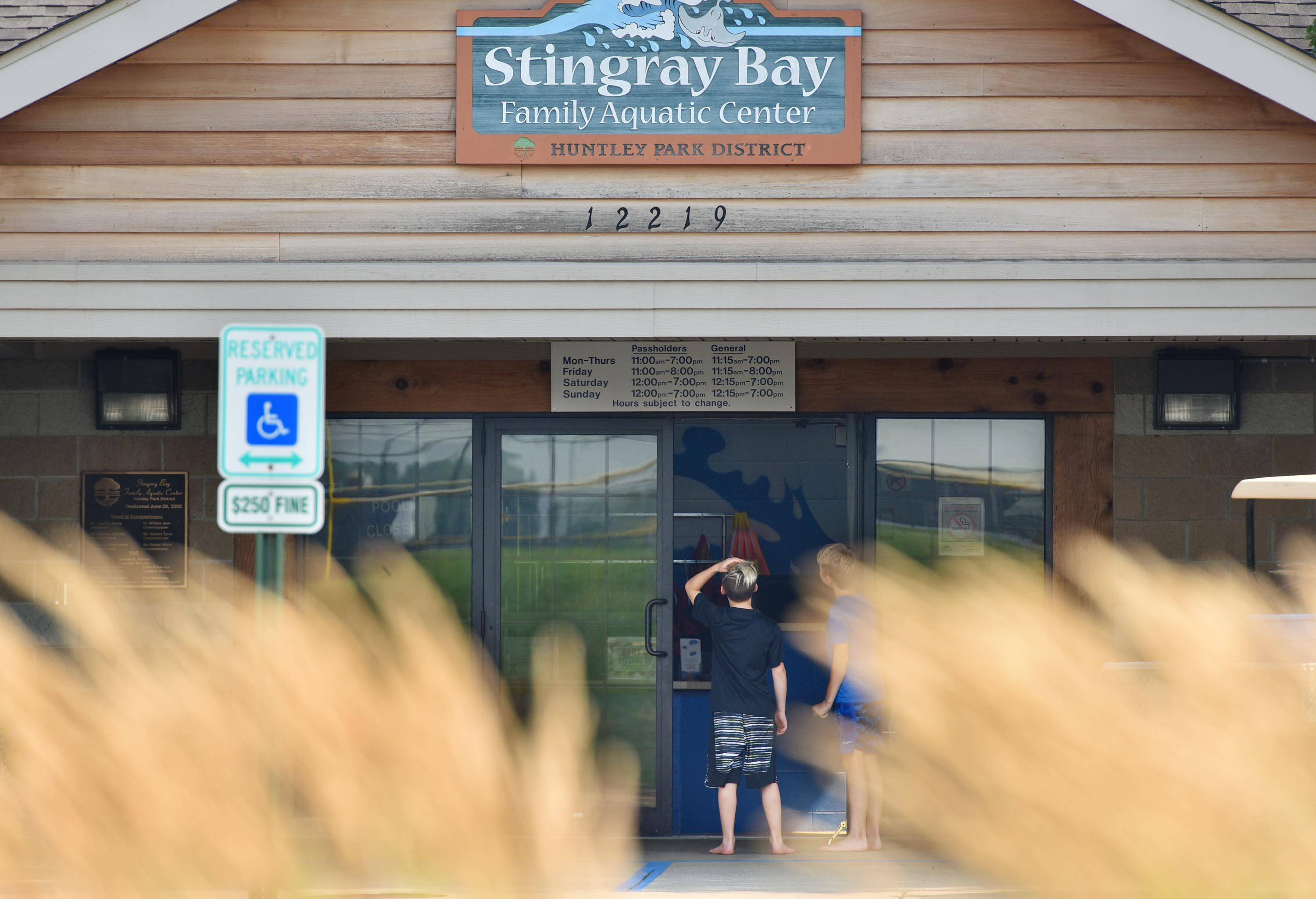 Two boys stand in the doorway Monday afternoon at Stingray Bay Aquatic Center in Huntley. Park district lifeguards pulled two swimmers in distress from the water. The girls were taken to Centegra Hospital-Huntley.