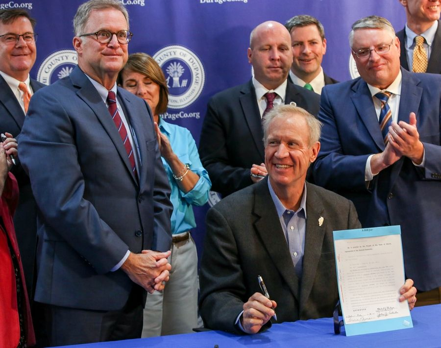 Gov. Bruce Rauner signs House Bill 5123 during a Monday ceremony in Wheaton attended by DuPage County Board Chairman Dan Cronin, County Clerk Paul Hinds, several county board members and some state lawmakers. The measure allows the county board to merge the local election commission with the county clerk's office.