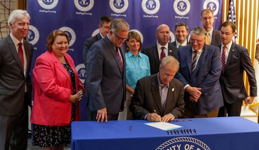 Gov. Bruce Rauner visited Wheaton on Monday to sign legislation that allows DuPage to merge the election commission with the county clerk's office.