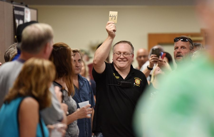 Post Cmdr. Dwane Lungren brings the winning envelope to the front of the room during the weekly drawing for the McHenry VFW Post 4600 Queen of Hearts game Tuesday. The Queen of Hearts card was not in the envelope, so the nearly $2.6 million jackpot will roll over.
