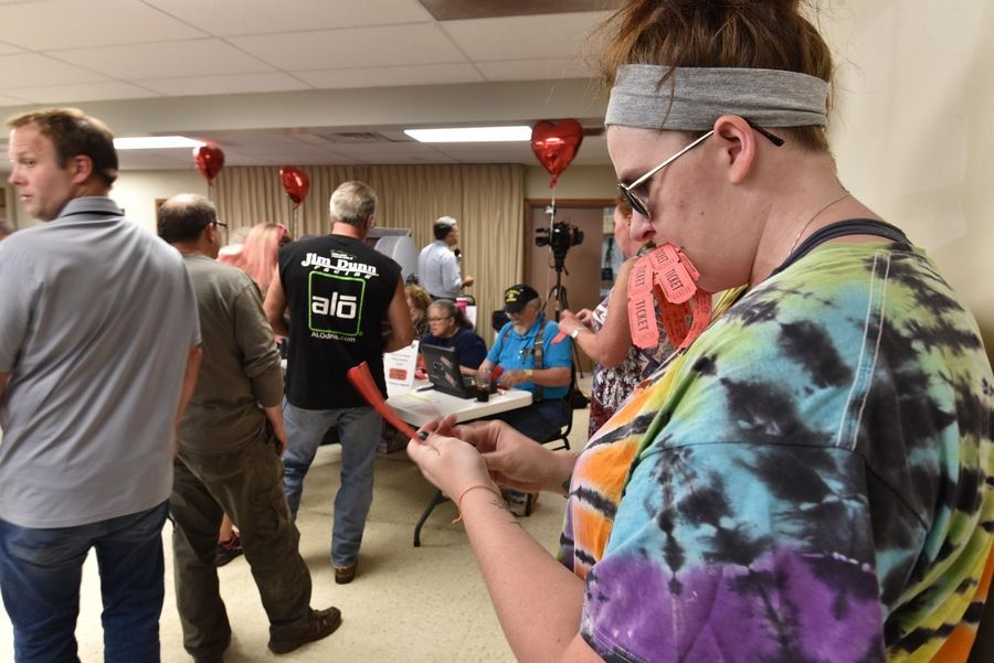 McHenry resident Samantha Kelly holds some of her tickets in her mouth at the weekly drawing for the McHenry VFW Post 4600 Queen of Hearts game Tuesday. She bought $20 worth.