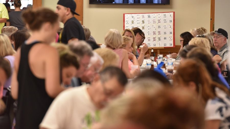 The game board is visible among the hundreds of people packed into the room two hours before the weekly drawing for the McHenry VFW Post 4600 Queen of Hearts game Tuesday.