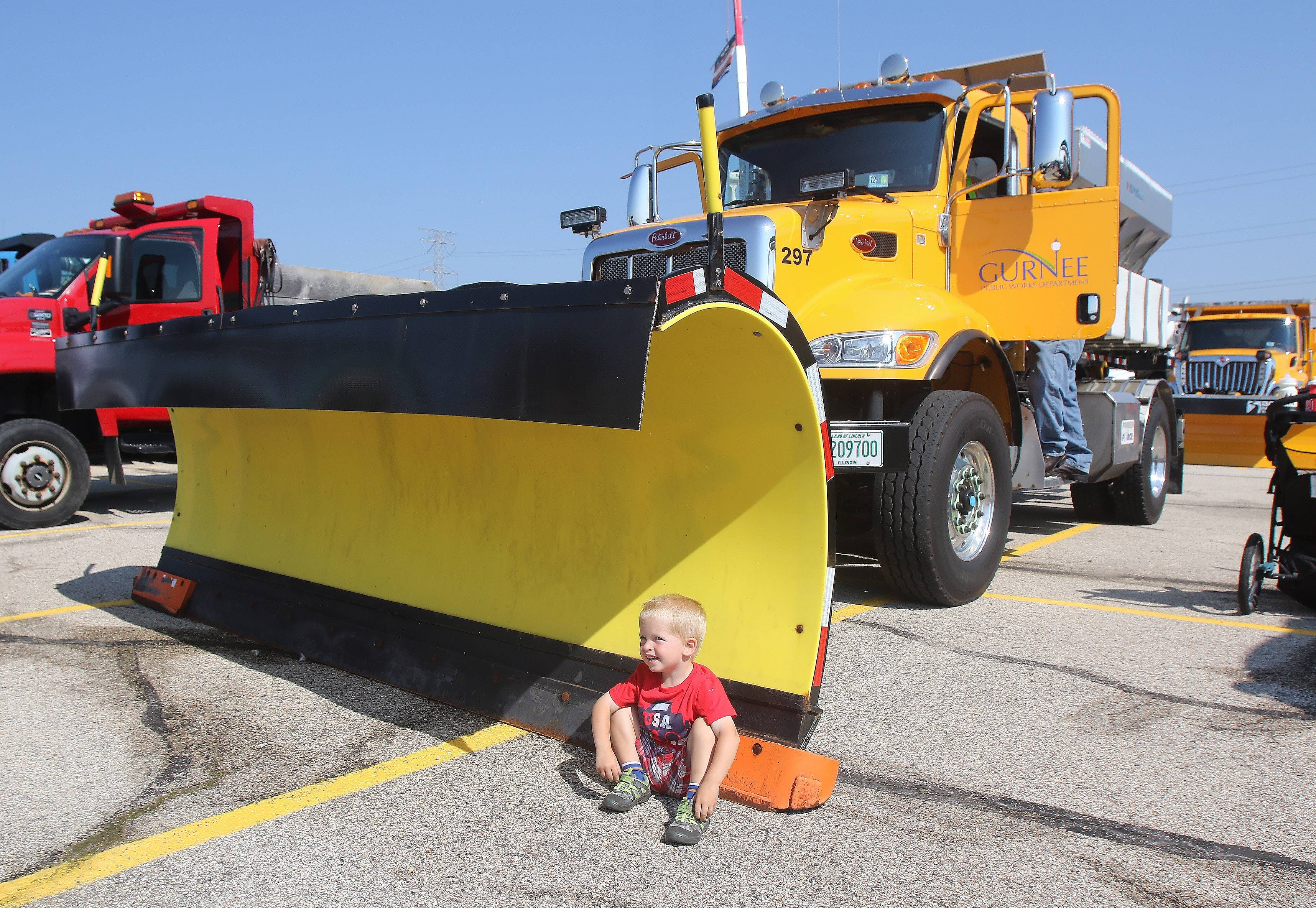 Liam Kessell, 2, of McHenry sits by the Gurnee Public Works Department snowplow at the Touch-A-Truck event Tuesday at the Lake County Fairgrounds. The drive was held in partnership with the American Public Works Association Lake Branch to promote public works workers as first responders.