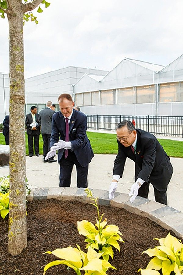 Valent Group Companies President Andy Lee, left, and Ray Nishimoto, president of parent company Sumitomo Chemical Company Health & Crop Sciences, plant a tree to signify future prosperity during the grand opening ceremony of Valent's new global research facility in Libertyville.
