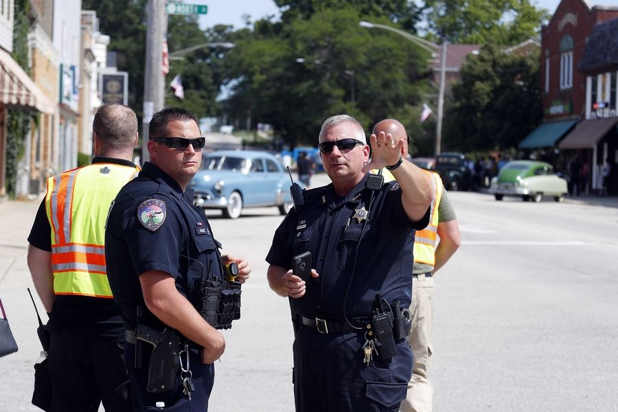 "Elburn Police Chief Nick Sikora, right, talks to Officer Eric Milnor about controlling traffic Wednesday as downtown Elburn is taken over for shooting the new HBO series ""Lovecraft Country."""