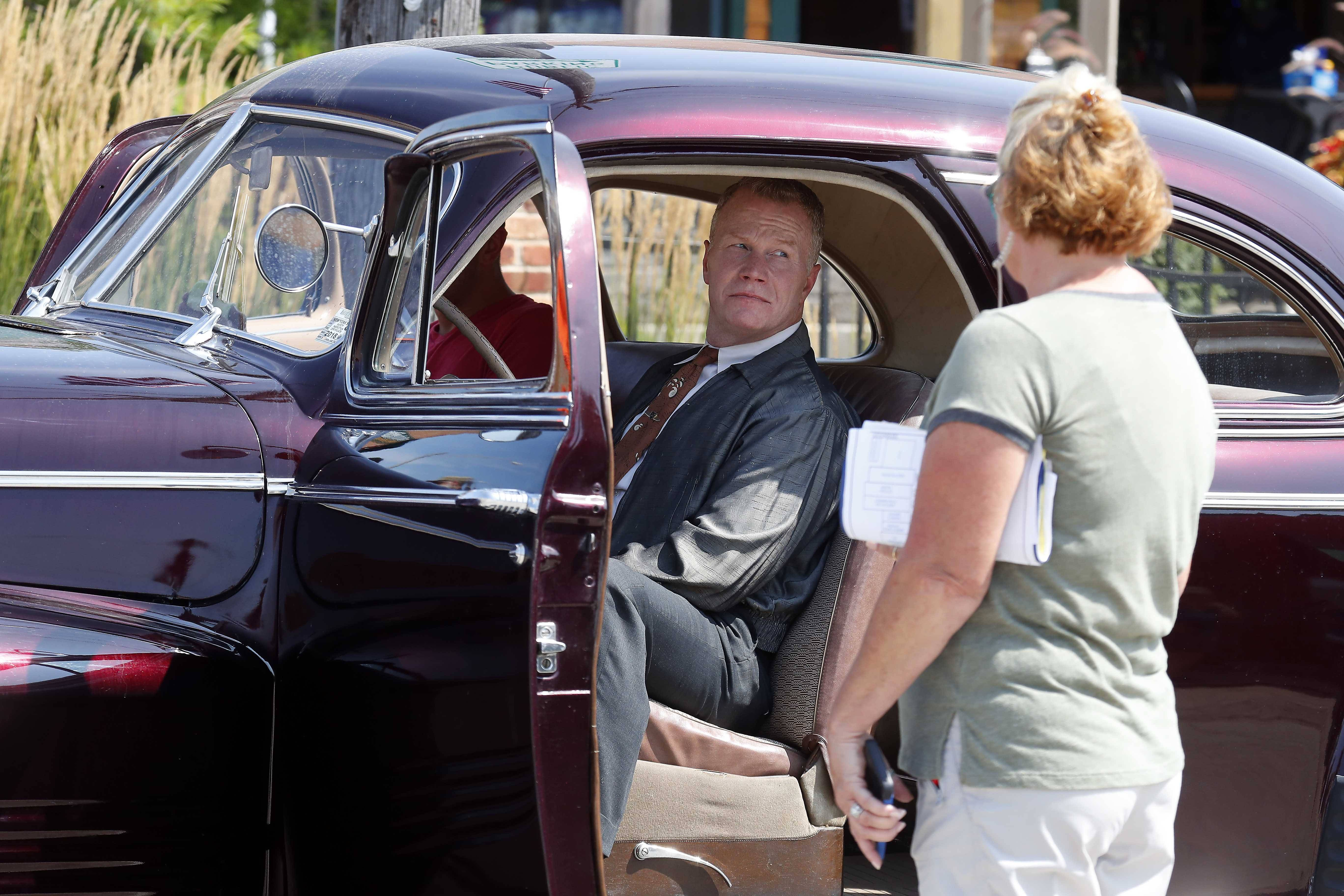 "Actor Charles Tiedje of Chicago waits to drive a Pontiac Silver Streak across North Main Street as Elburn is transformed for the HBO series, ""Lovecraft Country"" Wednesday."