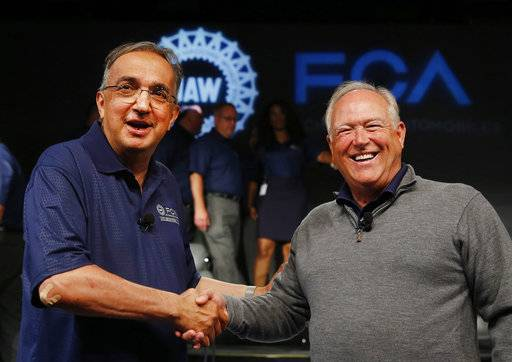 FILE - In this July 14, 2015, file photo, Fiat Chrysler Automobiles CEO Sergio Marchionne, left, and United Auto Workers President Dennis Williams shake hands during a ceremony to mark the opening of contract negotiations in Detroit. TOn Wednesday, July 25, 2018, holding company of Fiat founding family said Sergio Marchionne, who oversaw turnarounds of Fiat and Chrysler, has died.