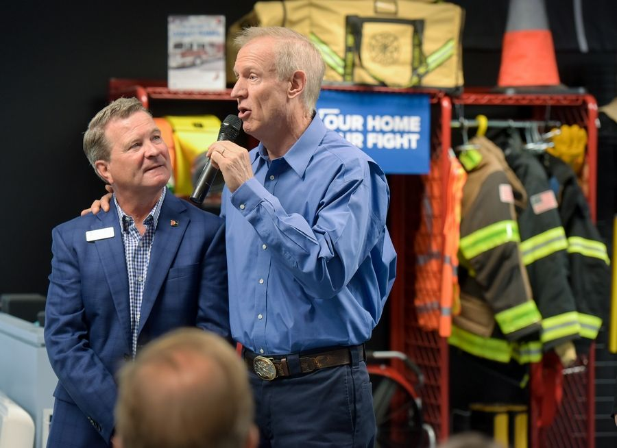 Paul Darley, president of W.S. Darley & Co., listens as Gov. Bruce Rauner talks about taxes during a visit to the 110-year-old Itasca company that makes fire trucks.