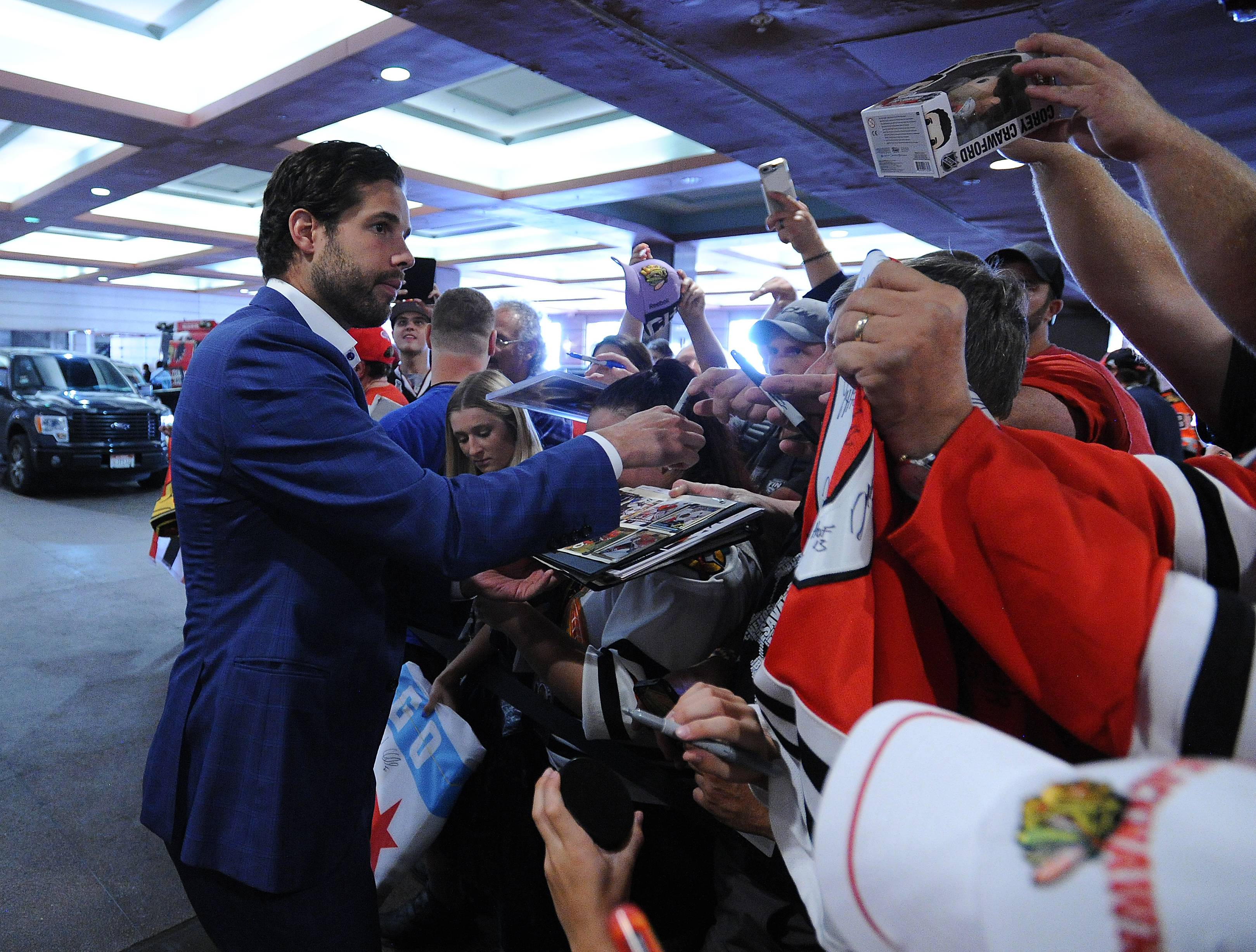 Mark Welsh/mwelsh@dailyherald.comBlackhawks Corey Crawford signs autographs for the fans after returning from missing half the season last year. He was in town for the 11th annual Blackhawks Convention in Chicago on Friday.