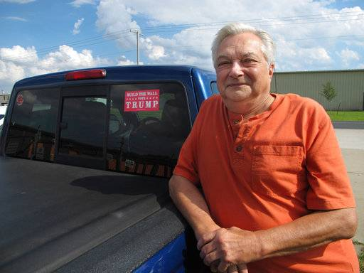"Bob Schrameyer stands next to his truck decorated with a ""Build The Wall - Vote Trump"" sticker in Goshen, Ind., on Thursday, May 31, 2018. A decade ago, Schrameyer and fellow Goshen residents lobbied police to partner with ICE, and pushed employers to vet workers' legal status. The problem, Schrameyer contends, is that many immigrants don't pay their fair share of taxes, while collecting welfare benefits."