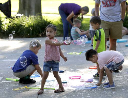 Children play on the grounds of the Elkhart County, Indiana Courthouse during the monthly First Fridays street festival on June 1, 2018. Attendance at the street festival reflects the county's growing racial and ethnic diversity.