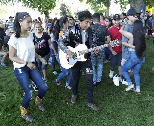 The lead guitarist from a local latino band leads a conga-style line of couples during the First Fridays street festival in Goshen, Ind., on June 1, 2018. Participants in the monthly gathering represent the diversity of the county.