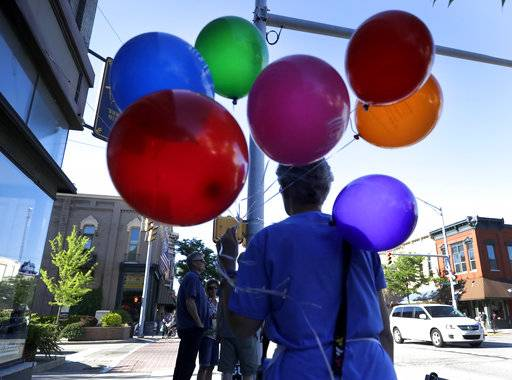 A woman carries multicolored balloons that she gave away to kids during the First Fridays street festival in Goshen, Ind., on Friday, June 1, 2018. Attendance at the gathering reflects the county's growing racial and ethnic diversity.