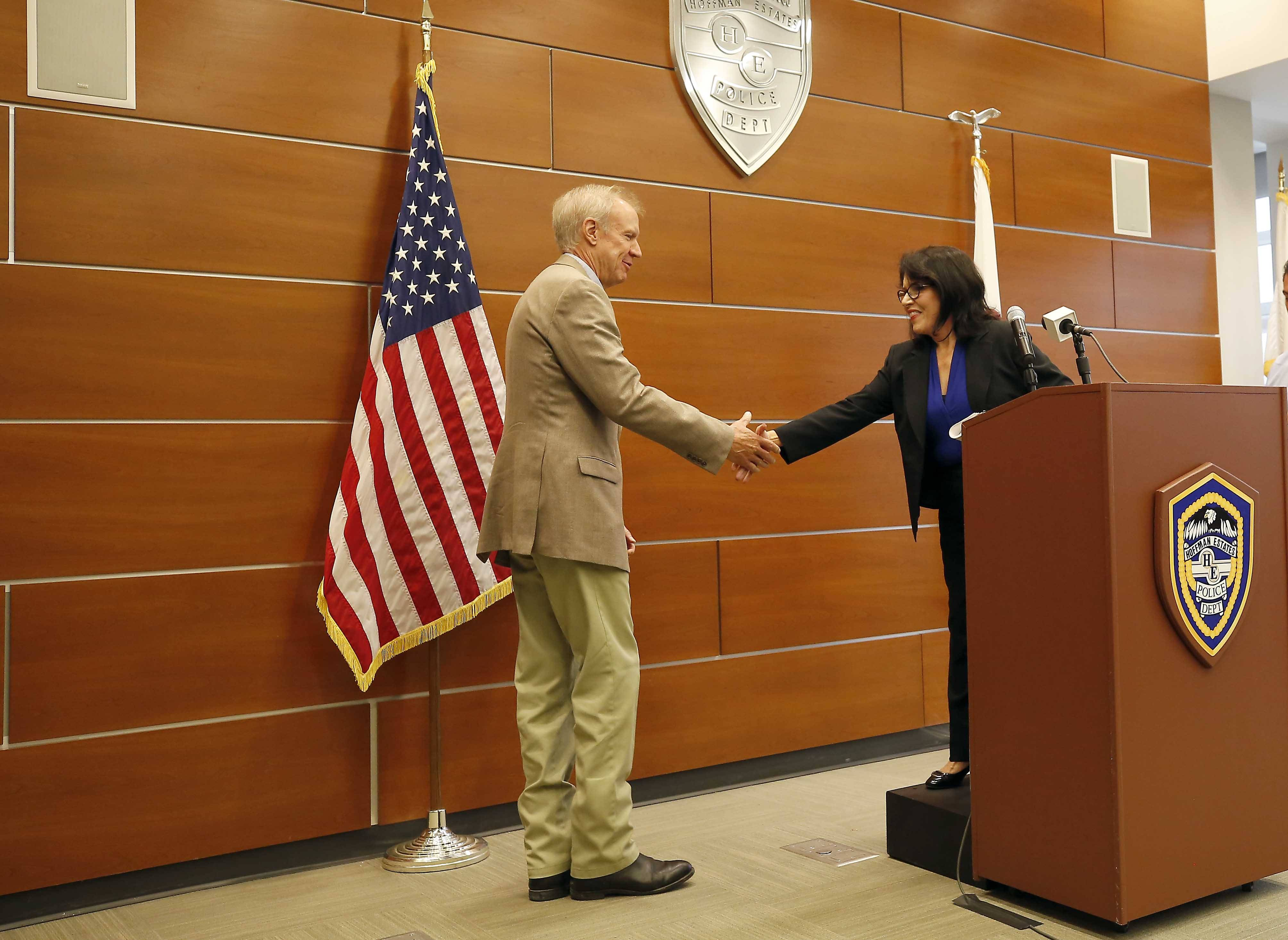 Lt. Gov. Evelyn Sanguinetti greets Gov. Bruce Rauner Tuesday at the Hoffman Estates Police Department, where they acknowledged the effectiveness of the Joint Emergency Management System.