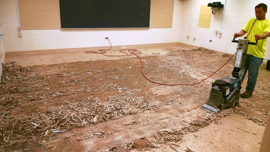 A worker prepares the floor of a classroom inside Crown School in Wauconda for new tile as part of a schoolwide project this summer.