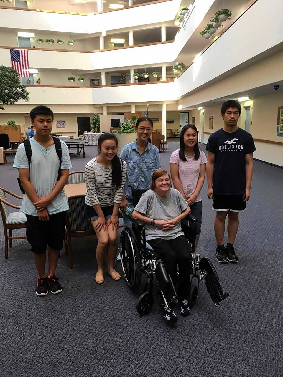Student volunteers from Team STEM for All with Greencastle of Barrington resident Carleen Fuller (front) after helping her. In back, from left, are Charles Lin (Conant High School); LeAnne Lin (Vernon Hills High School); Alisa Wang, Emily Lu and Gavin Yuan (Adlai E. Stevenson High School).