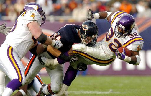 FILE - In this Dec. 5, 2004, file photo, Minnesota Vikings running back Onterrio Smith (32) is brought down by Chicago Bears linebacker Brian Urlacher (54) after catching a pass for a 9-yard gain as Vikings' Cory Withrow, left, helps out during the second quarter of an NFL football game in Chicago. Urlacher will be inducted into the Pro Football Hall of Fame in Canton, Ohio on Saturday, Aug. 4, 2018.