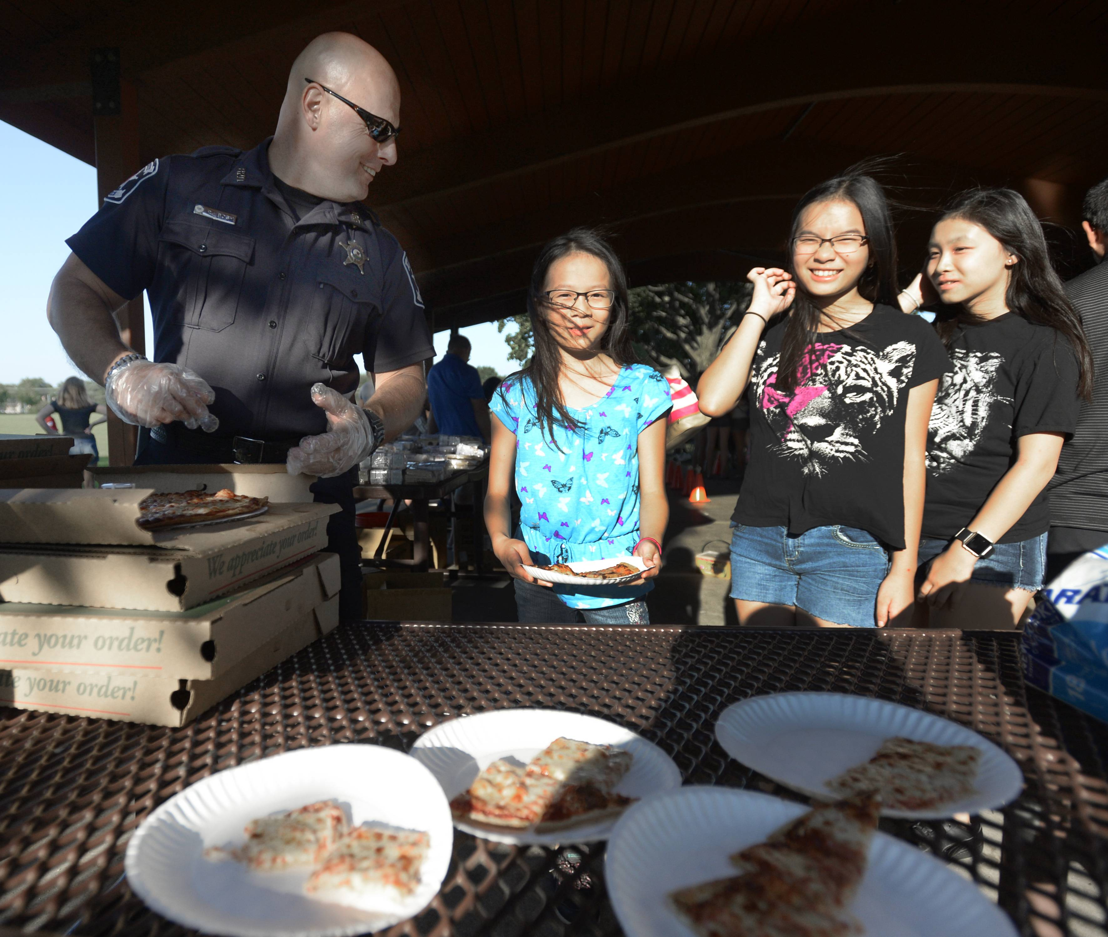Bartlett police officer Rich Bosh treats participants of last year's National Night Out Family Fun Night to pizza at the Jim Jensen Pavilion.