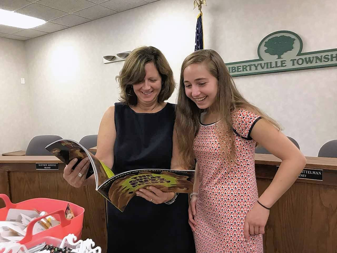 Sofia Coury, 15, and her Girl Scout Gold Award adviser Libertyville Township Supervisor Kathleen O'Connor look over a book that will be included in a Reading Gear Literacy Kit.