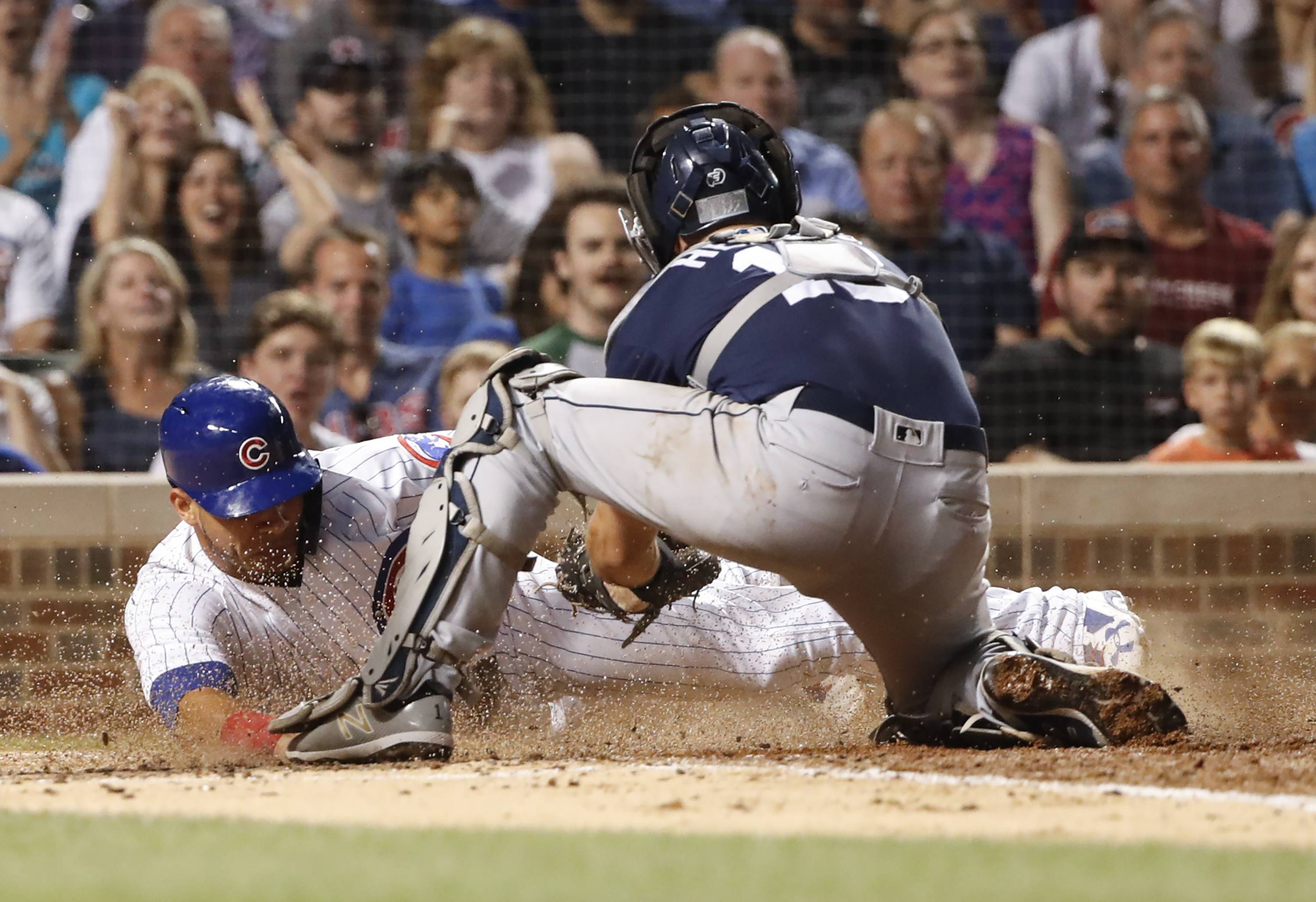 Chicago Cubs' Willson Contreras, left, scores as San Diego Padres' Austin Hedges tries to make the tag during the fifth inning on Thursday at Wrigley Field.