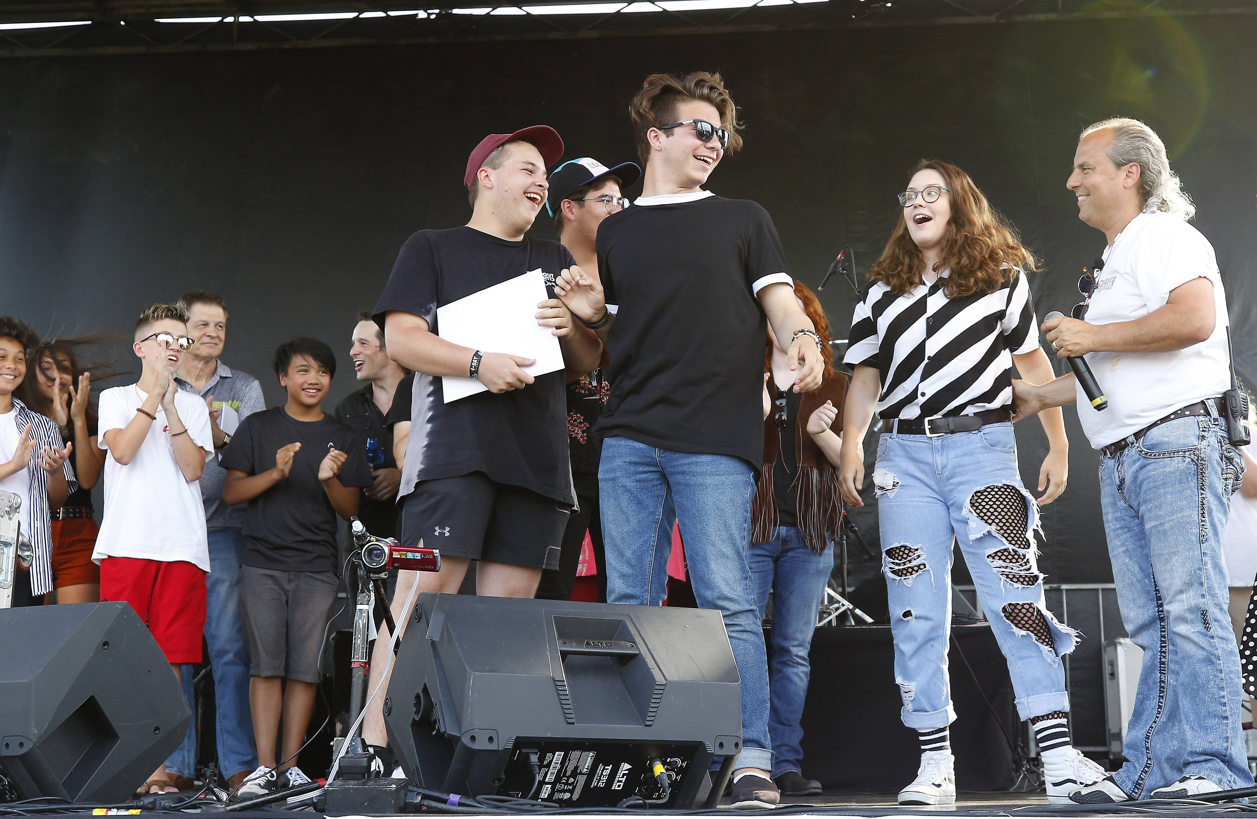 Ron Onesti talks to Seasalt members Jon O'Brien of Richmond, Becky Sargeant of Woodstock, Kayla Seeber of Poplar Grove and Drew Zaremba of Richmond after they were announced as the winner of Suburban Chicago's Got Talent Saturday at Addison's Little Italy Fest-West.