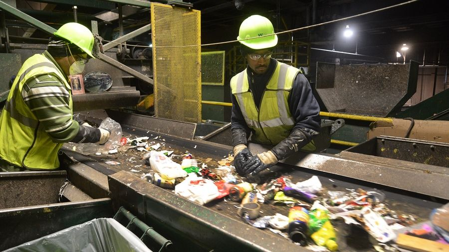 Sorters sift through the refuse, rejecting items that cannot be recycled, at the Waste Management recycling facility in Grayslake.