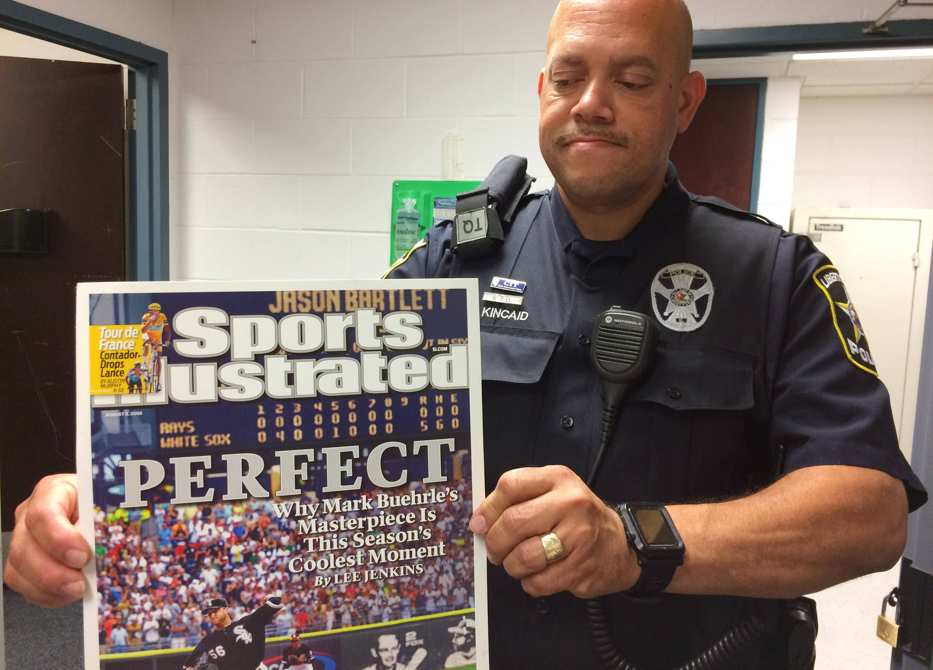 Libertyville Police Officer Wayne Kincaid, an evidence custodian, displays one of the posters included in a variety of sports memorabilia that has been stored at the station.