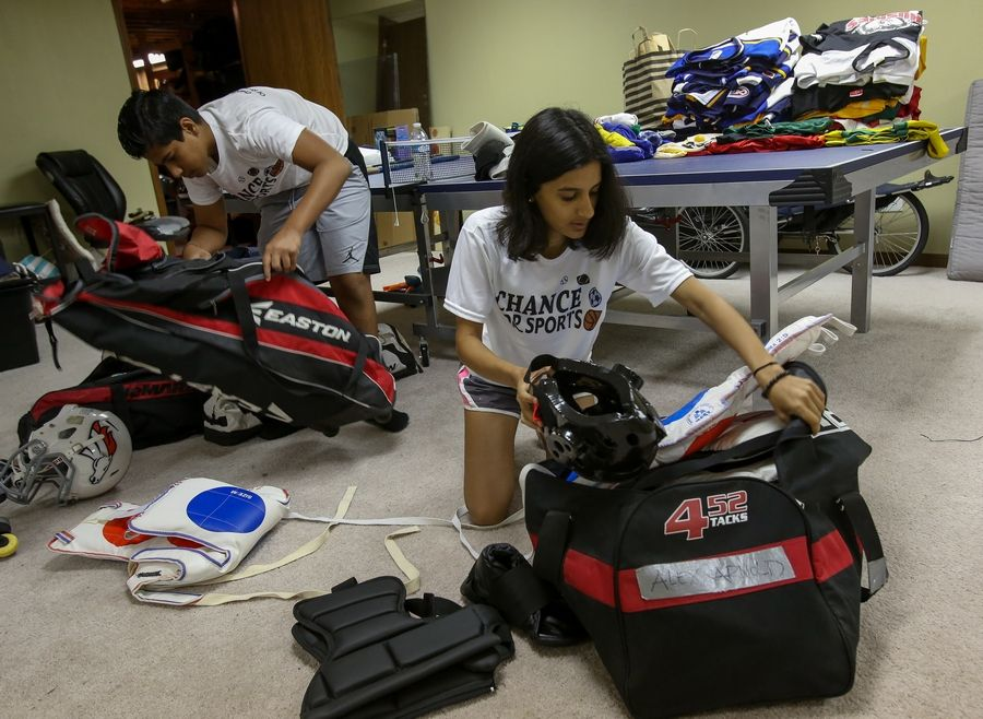 Anuva Shandilya gets help from her brother, Daksh, to sort through some of the sports equipment she has collected through her nonprofit organization, Chance For Sports. The family's Naperville basement serves as a warehouse for donated gear until she arranges to donate it to local and international organizations that serve children.