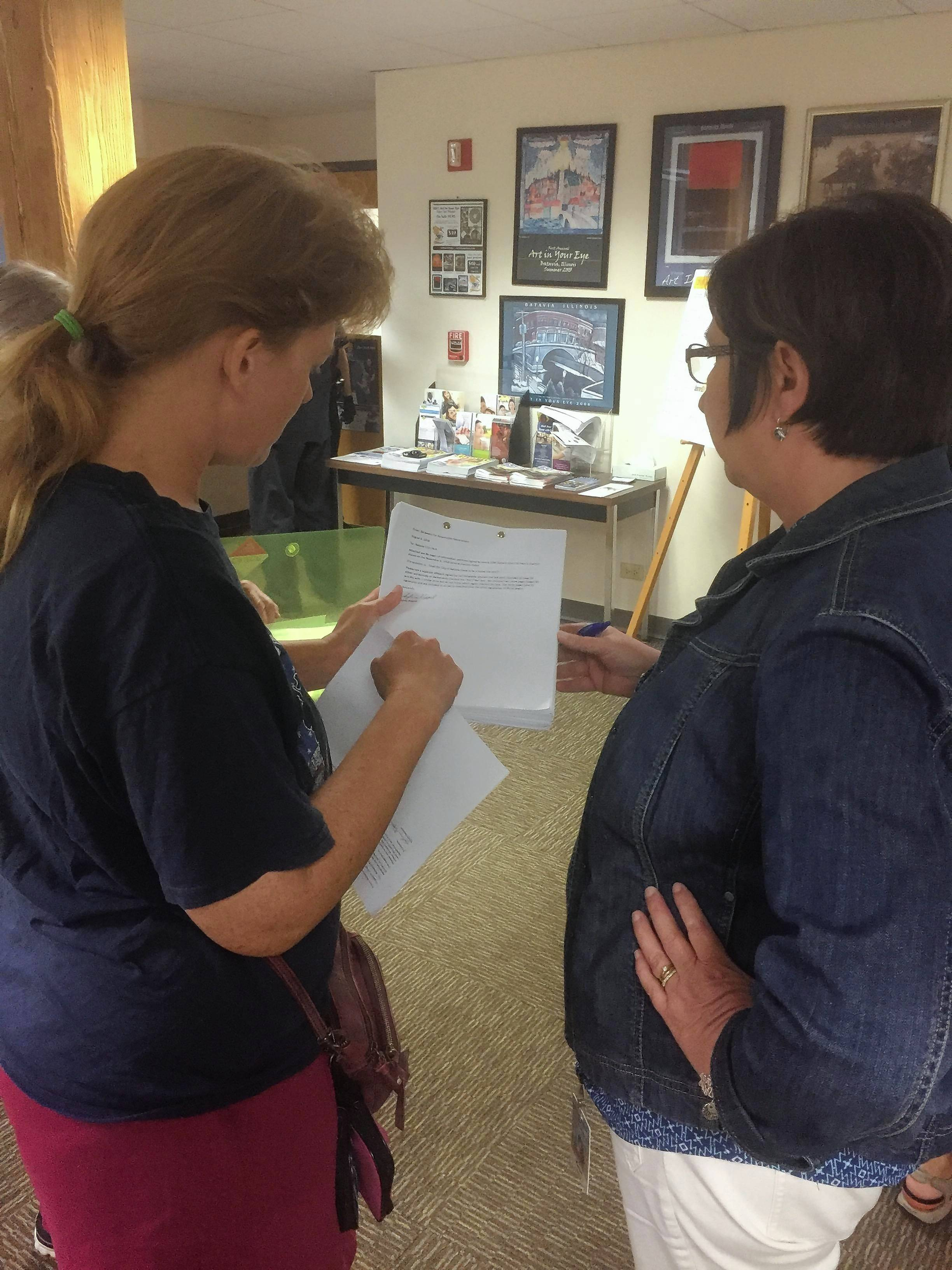 Sylvia Keppel of Batavia, left, explains to city administrative assistant Karen Morley an affidavit she submitted Monday along with a petition for a referendum question to remove the city's home-rule authority.
