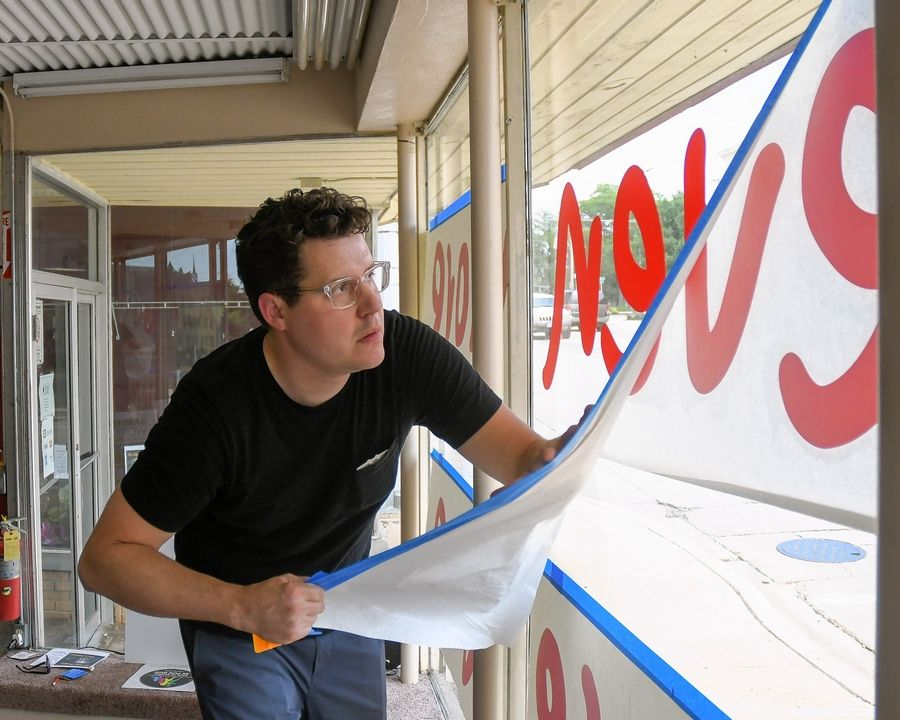 "Chicago artist Matthew Hoffman prepares a window display in downtown West Chicago's Gallery 200 to promote the dedication for ""loveevenmore,"" a sculpture to be installed Wednesday on the grounds of the West Chicago Public Library."