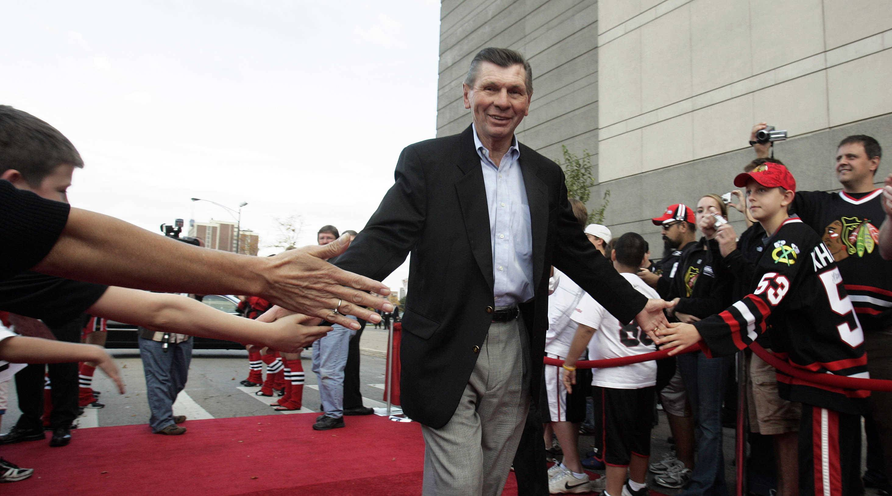 STEVE LUNDY/slundy@dailyherald.com Chicago Blackhawks legend Stan Mikita high-fives fans as he comes down the red carpet during a ceremony prior to the home opener at the United Center in 2008.