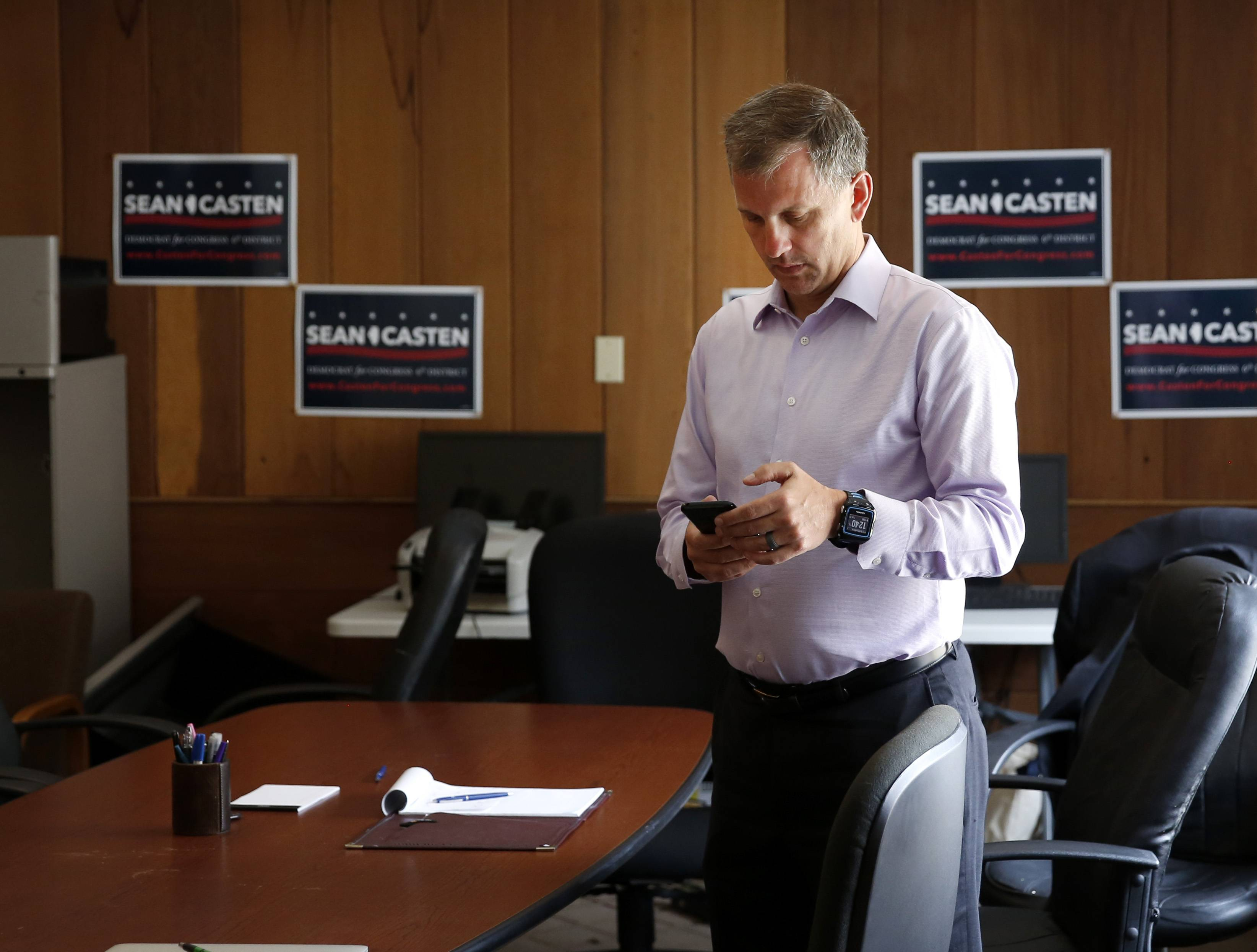 Sean Casten checks his messages after meeting with members of a constituent group about health care concerns during a summer day on the campaign trail.