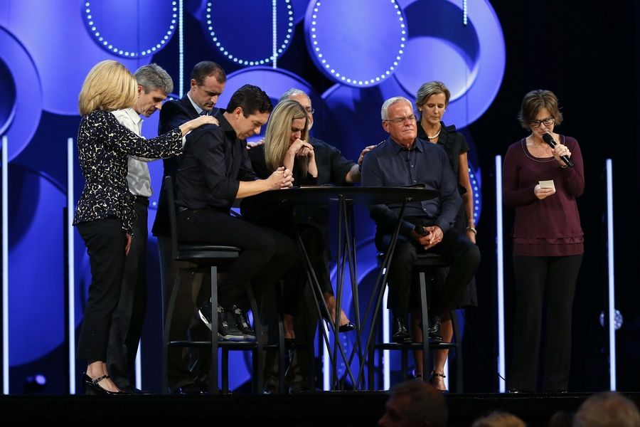 The elders of the church pray with Steve Carter, 38, Heather Larson, 42, and Bill Hybels at a gathering last fall.