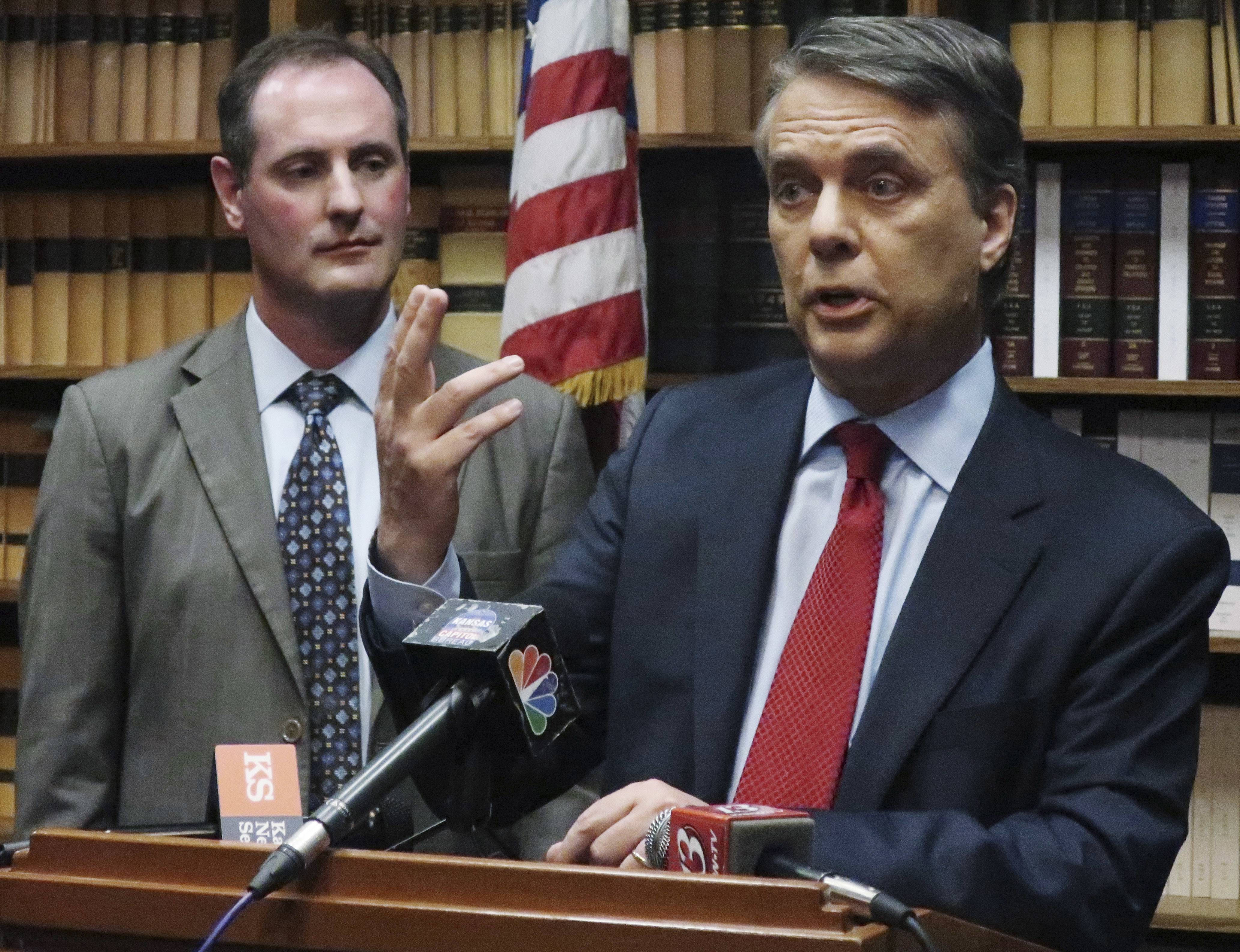 FILE - In this May 30, 2018, file photo, Kansas Gov. Jeff Colyer, right, answers a question from reporters as Lt. Gov. Tracey Mann, left, listens during a news conference in Topeka, Kan. Colyer and immigration hardliner Kris Kobach were virtually tied atop a seven-candidate field with nearly two-thirds of the precincts counted in the primary, late Tuesday, Aug. 7, 2018.
