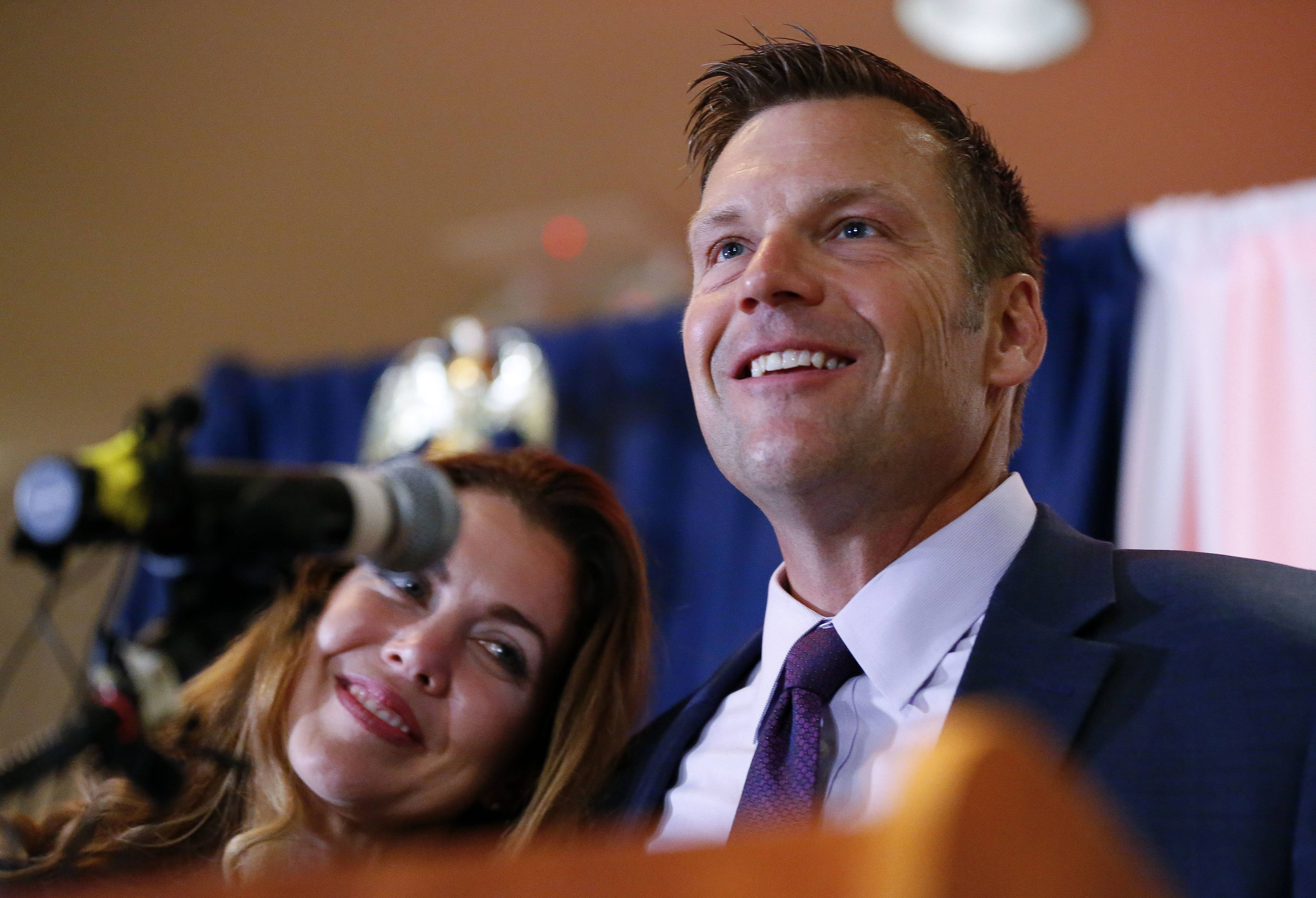Kansas Republican gubernatorial candidate Kris Kobach and his wife, Heather, take the stage to thank their supporters and send them home for the night after problems with polls in Johnson County, Kan., delayed the final results until the early morning on Wednesday, Aug. 8, 2018, at the Capitol Plaza Hotel in Topeka, Kan. (Chris Neal/The Topeka Capital-Journal via AP)