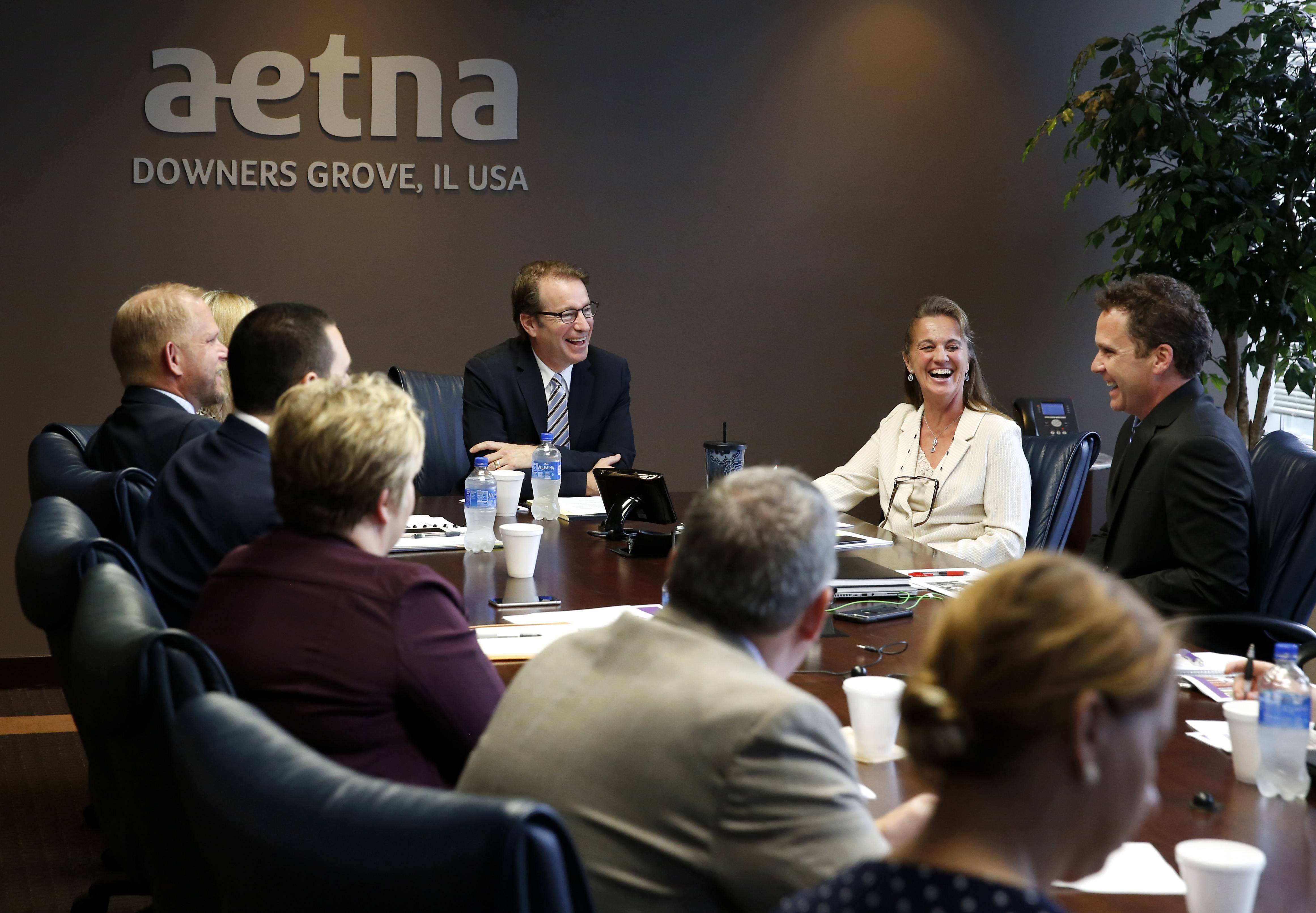 U.S. Rep. Peter Roskam of Wheaton, center, listens to Aetna health care executives discuss their response to the opioid crisis as he visits with them on the campaign trail in Downers Grove.