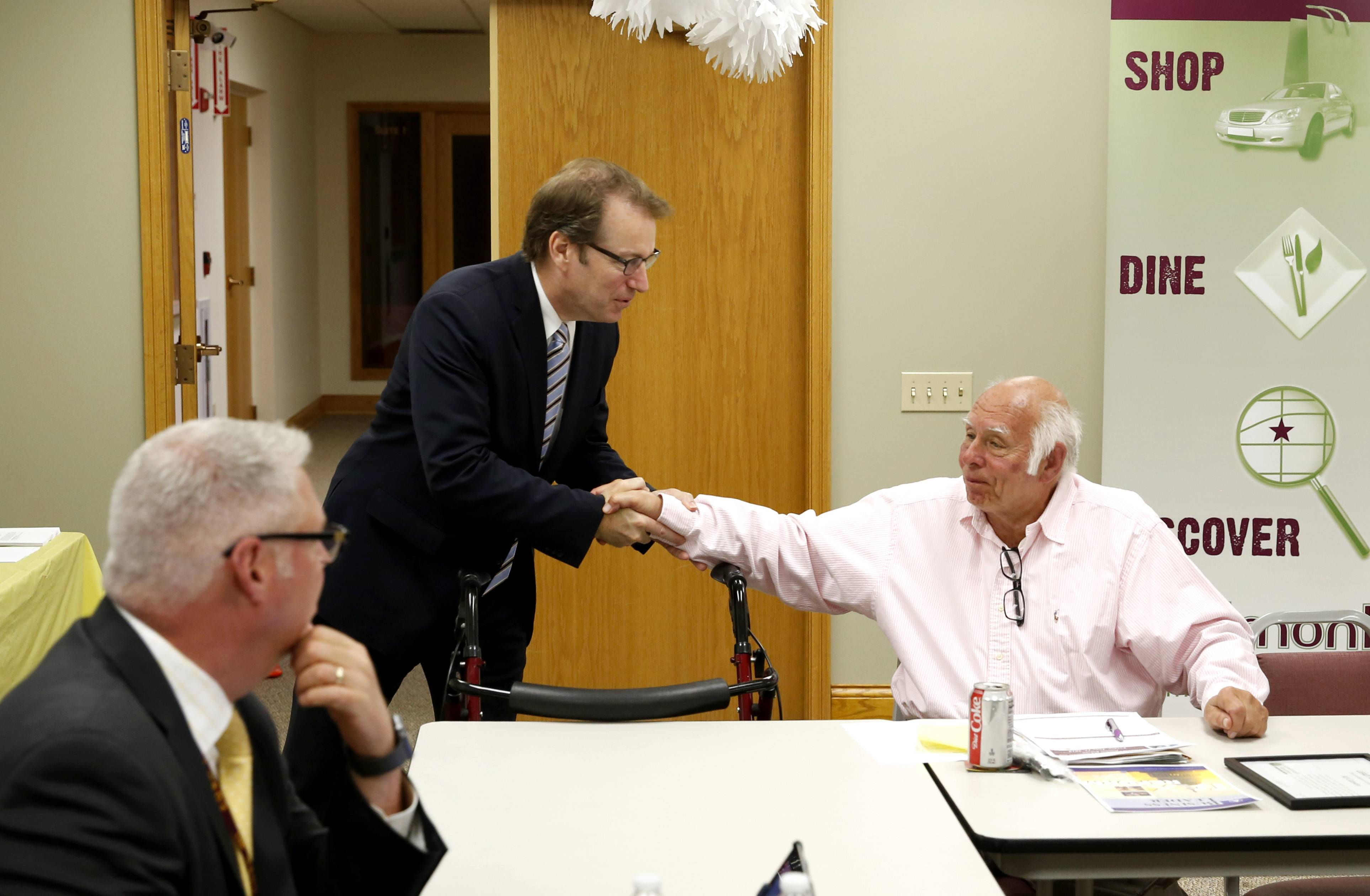 U.S. Rep. Peter Roskam greets Al Carson at the Westmont Centre for a Westmont Chamber of Commerce and Tourism Bureau roundtable, where topics included health insurance, taxes and trade relations with China.