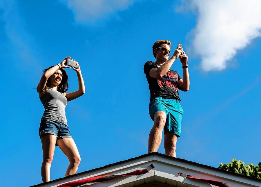 Two Palatine High School Marching Band alumni watch the end of band camp parade from the roof of a house in Palatine Aug. 2.