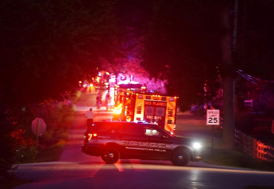 Police close Spring Creek Road at Moate Lane west of Barrington Wednesday night as emergency crews work a garage fire on Ridgecroft Lane.