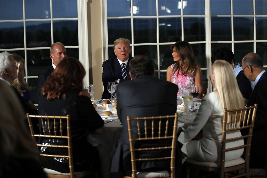 President Donald Trump sits with first lady Melania Trump as he meets with business leaders, Tuesday, Aug. 7, 2018, at Trump National Golf Club in Bedminster, N.J.