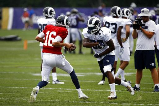 Los Angeles Rams running back Todd Gurley, right, runs a drill with quarterback Jared Goff during a joint NFL football training camp practice at the Baltimore Raven's headquarters, Tuesday, Aug. 7, 2018, in Owings Mills, Md.