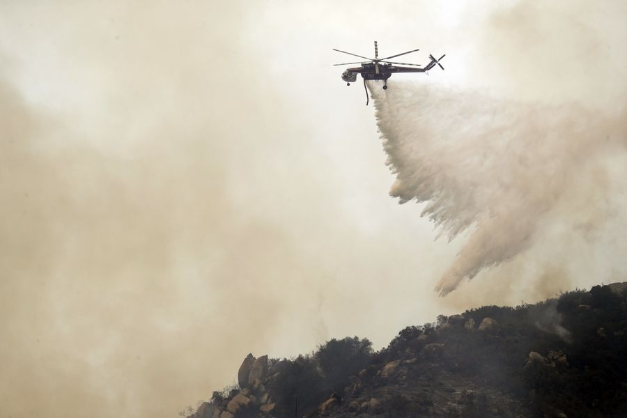 A helicopter drops water onto a ridge top as part of efforts to fight a wildfire Friday in Lake Elsinore, California.