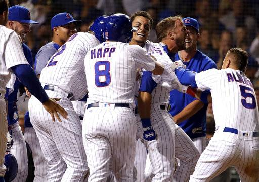 Chicago Cubs' David Bote, second from right, reacts as he celebrates with teammates after hitting the game-winning grand slam during the ninth inning of a baseball game against the Washington Nationals, Sunday, Aug. 12, 2018, in Chicago. The Cubs won 4-3.
